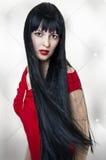 Schöner Brunette mit dem langen Haar und rotem Kleid Stockfoto
