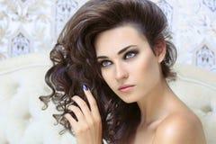 Schöner Brunette mit einem langen gelockten Haar Stockbilder