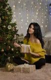 Schöner Brunette mit einem Weihnachtsbaum und einem Geschenk Lizenzfreie Stockfotografie