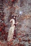 Schöner Brunette mit gemaltem Gesicht, Kleidungsmedizinmann, ein Blumenkranz auf ihrem Kopf und Hörner, ein glühendes hölzernes P Stockbilder