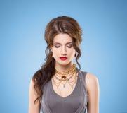 Schöner Brunette mit rotem Lippenstift und goldener Luxushalskette Stockfotos