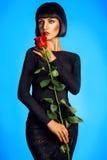 Schöner Brunette mit Rotrose stockfoto