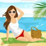 Schöner Brunette mit Sonnenbrille ein Sonnenbad nehmend auf dem Strand, der auf einem Tuch sitzt lizenzfreie abbildung