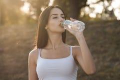 Schöner Brunette trinkt Wasser von einer Flasche lizenzfreie stockbilder