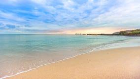 Schöner bunter Sonnenaufgang am Strand mit bewölktem Himmel Lizenzfreies Stockfoto