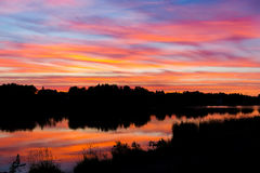 Schöner bunter Sonnenuntergang Der Himmel schimmert in den verschiedenen Farben Ein kann die Schattenbilder von Bäumen und von Hä Lizenzfreie Stockfotografie