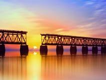 Schöner bunter Sonnenuntergang oder Sonnenaufgang mit defekter Brücke und bewölktem Himmel stockfotografie