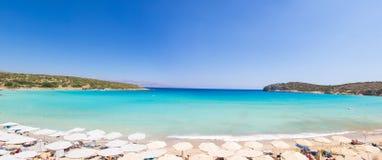 Schöner bunter Strand in Kreta-Insel, Griechenland Voulisma-Paradiesstrand mit Regenschirm und sunbeds lizenzfreie stockbilder