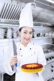 Chef hält Messer und Nachtisch Stockbild
