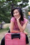 Schöner Chinese, der glücklich auf ihren Koffer wartet Lizenzfreie Stockfotografie