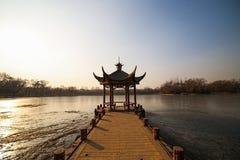 Schöner chinesischer Gazebo mitten in einem gefrorenen See im Park auf einem Hintergrund von Bäumen Lizenzfreie Stockbilder