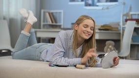 Schöner Damenstudent, der glücklich im Spiegel schaut, bilden zuerst, Jugendschönheit stock video footage