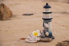 Schöner Dekor in Form eines Leuchtturmes und Muscheln auf dem Sand mit Raum für den Text stockbild