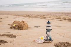 Schöner Dekor in Form eines Leuchtturmes und Muscheln auf dem Sand mit Raum für den Text lizenzfreies stockbild