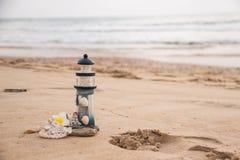 Schöner Dekor in Form eines Leuchtturmes und Muscheln auf dem Sand mit Raum für den Text stockfotos