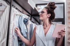 Schöner Designer, der stilvolle Ohrringe und den Anhänger betrachtet ihre Kleider trägt stockbilder