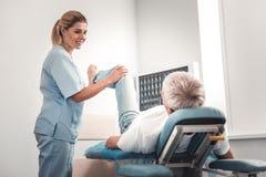 Schöner Doktor, der Beinübungen für Mann tut stockfoto