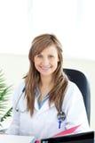 Schöner Doktor, der in einem Büro sitzt Stockbilder