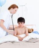 Schöner Doktor, der einen kleinen Jungen überprüft Lizenzfreies Stockfoto