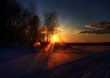 Schöner gefrorener Winterseesonnenuntergang mit Wald und Wolken Stockbild
