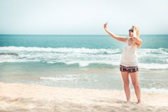 Schöner einsamer Frauenreisender auf dem Strand, der Bild selfie am Telefon während der Strandreisefeiertage nimmt, machen für So lizenzfreie stockfotografie