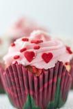 Schöner einzelner kleiner Kuchen mit Zuckerglasur und weniger roter Herzsüßigkeit Stockbilder