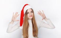 Schöner emotionaler blonder weiblicher vorbildlicher Abnutzung Santa Claus-Hut Weihnachts- und guten Rutsch ins Neue Jahr-Grußkon Lizenzfreie Stockfotos
