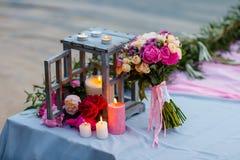 Schöner, empfindlicher Brautblumenstrauß unter Dekoration mit Kerzen Stockbild