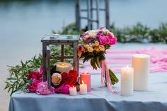 Schöner, empfindlicher Brautblumenstrauß unter Dekoration mit Kerzen und frische Blumen Stockfoto