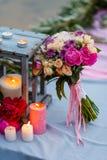 Schöner, empfindlicher Brautblumenstrauß unter Dekoration mit Kerzen und frische Blumen Stockbild