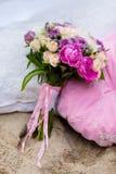 Schöner, empfindlicher Brautblumenstrauß unter Dekorationen mit Kissen Stockfotografie