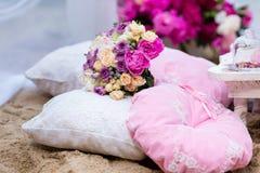 Schöner, empfindlicher Brautblumenstrauß unter Dekorationen mit Kissen Lizenzfreie Stockfotos