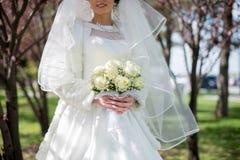 Schöner empfindlicher Brautblumenstrauß von weißen Rosen und von Blumen in den Händen der Braut Lizenzfreies Stockbild