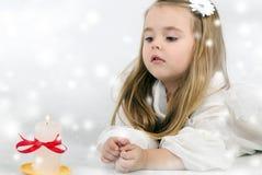 Schöner Engel des kleinen Mädchens mit einer Kerze Stockfotografie