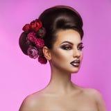 Schöner erwachsener Brunette mit bilden Frisur und Blumen in h Stockbild