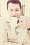 Schöner erwachsener Mann, der das Aroma einer Schale von frischem heißem savouring ist stockfoto