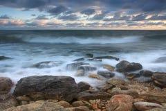 Schöner felsiger Seestrand am Sonnenuntergang Lizenzfreies Stockbild