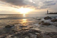 Schöner felsiger Seestrand am Sonnenuntergang mit dem L Lizenzfreies Stockbild