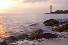 Schöner felsiger Seestrand am Sonnenuntergang mit dem L Stockfotografie