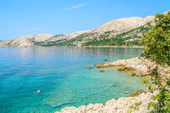 Schöner felsiger Strand mit haarscharfem Meer- und Leute snorkeli Lizenzfreie Stockfotografie