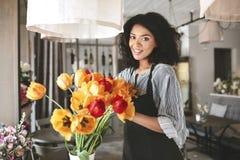 Schöner Florist im Schutzblech, das mit Blumen arbeitet Junges Afroamerikanermädchen, das Blumenstrauß von Tulpen herstellt stockfotos