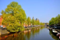 Schöner Flusskanal mit Booten und grünen Bäumen in Amsterdam, Holland Netherlands lizenzfreies stockbild