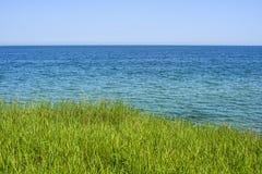 Schöner Frühlingsmeerblick mit grünem Gras Stockbilder
