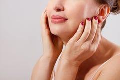 Schöner Frauengesichtsabschluß oben Antialterskonzept Kollagen und plastische Chirurgie Frau, die ihr Gesicht berührt Rote Manikü Stockbilder