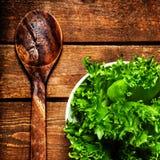 Schöner frischer Salat in einem Teller mit hölzernem Löffel über Weinlese flehen an Stockbild