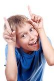Schöner froher frecher Junge in einem blauen T-Shirt, das herum täuscht Stockfotos