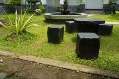 Schöner Garten mit der Bank gemacht vom Stein, vom Brunnen und vom Altbau im Batik-Museum Foto eingelassenes Pekalongan Lizenzfreie Stockbilder
