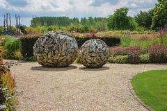 Schöner Garten verziert mit 2 hölzernen Bällen Stockfotografie