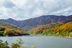 Schöner Gebirgssee im Tal der Hügel, im Herbst, unter Tausenden der bunten Bäume stockfotografie