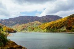 Schöner Gebirgssee im Tal der Hügel, im Herbst, unter Tausenden der bunten Bäume lizenzfreie stockfotos